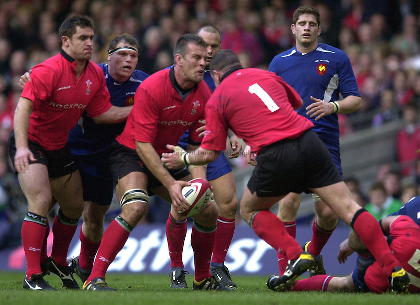 Photo. © Peter Spurrier/Richard Lane Photography.07/03/2004 Six Nations Rugby - Wales v France.Gareth Llewellyn hold's the ball in as Iestyn Thomas moves in to collect the ball...