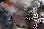 A Town of Manchester CT  firefighter looks away from the stream of hot smoke pouring from a vent hole he just made during a 2 alarm house fire in Manchester, Thuursday June 2, 2004. There were no reported injuries but 1 dog was rescued from the house and treated on scene by medical personnel. (AP Photo/Journal Inquirer, Jim Michaud)