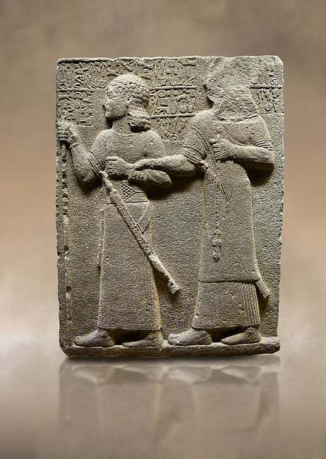 """Photo of Hittite monumental relief sculpted orthostat stone panel of Royal Buttress. Basalt, Karkamıs, (Kargamıs), Carchemish (Karkemish), 900-700 B.C. Anatolian Civilisations Museum, Ankara, Turkey.<br /> <br /> King Araras holds his son Kamanis from the wrist. King carries a sceptre in his hand and a sword at his waist while the prince leans on a stick and carries a sword on his shoulder. <br /> <br /> Hieroglyphs reads; """"This is Kamanis and his siblings. I held his hand and despite the fact that he is a child, I located him on the temple. This is Yariris' image"""".  <br /> <br /> Against a brown art background."""