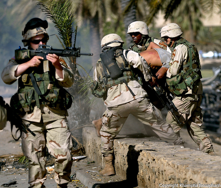 1st Cavalry Divison soldiers arrest an Iraqi while another soldier try to keep a hostile crowd back during a riot in central Baghdad on June 14, 2004.  (photo by Khampha Bouaphanh)