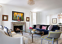 A spacious living room styled in a traditional manner. An upholstered sofa and armchairs are arranged around a glass topped coffee table in front of a fireplace. A separate dining area is seen through an opening to one side. A bold modern painting above the fireplace adds a contemporary touch.