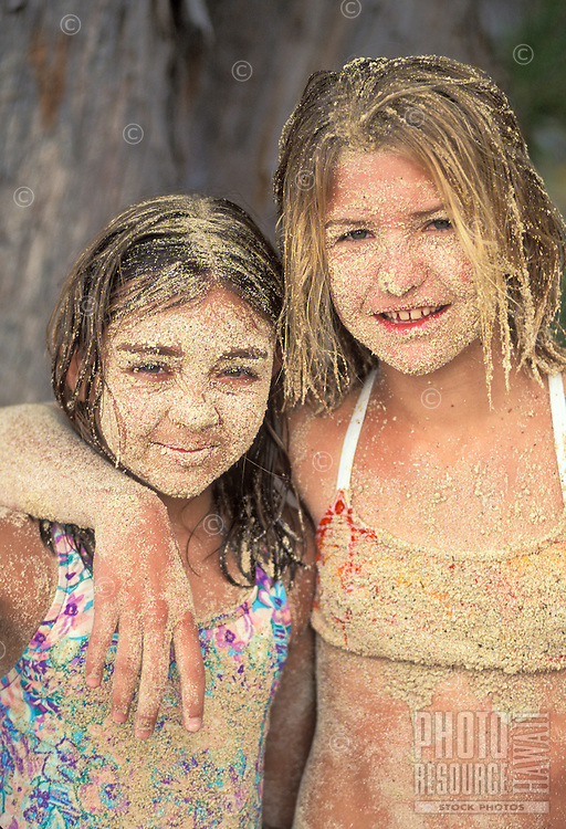 Two young girls with sand covering their faces while playing at the beach