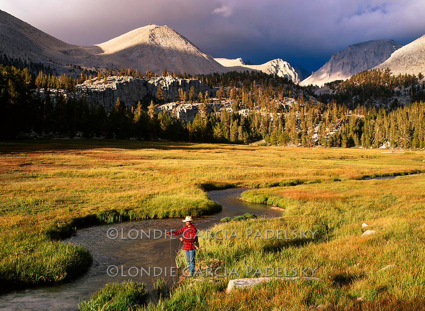 Fly fishing on the west slope of Sierra Nevada at Crabtree Meadow-storm clouds over Mt Whitney in the background. Sequoia National Park, California