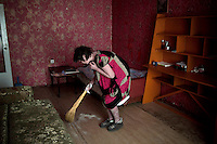 Elena Shershova, who suffers from severe psoriasis, sweeps up dead skin in her tiny apartment. She has regular appointments in Blagoveshchensk, a town some 16 hours on the train from her home.<br /> People in villages Verkhnezeysk rely heavily on the medical services offered by the Matvei Mudrov medical train. <br /> <br /> The Matvei Mudrov train is a medical train operated by Russian Railways along the course of the Baikal Amur Magistral (Baikal-Amur Mainline, or BAM) railway line. Named after a famous 19th century Russian physician, the train employs around 15 doctors who make about 10 trips a year, each lasting two weeks. Along the way they deliver essential medical services to people living in remote villages along the 4,324 km long BAM railway. Though not equipped to carry out surgical procedures the train has heart monitors, ultrasound and x-ray machines to deliver diagnosis.