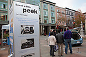 Poster reading ' Sneak a little peek'. Nissan Leaf Zero Emission Tour promotional event for the Nissan Leaf electric car that is scheduled to be released in Fall 2010. Car specs from Nissan: 5 person capacity, 90 MPH top speed, lithium-ion battery, 100 mile average range per charge. Santana Row, San Jose, California, USA, 12/5/09