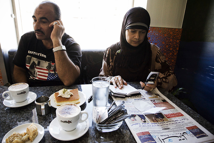 Mamdouh Habib and his wife, Maha, make campaing calls on their mobile phones at a cafe in Granville, western Sydney, March 2007. Much of the Habib campaign's organisation was completed via mobile phones by a team of four volunteers while on the road around western Sydney. Photo: Ed Giles.