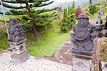 Stone statues of strong men guard the path by which the stupa is entered.  The stupa is found in the midst of extensive yard and gardens at the top of several flights of stairs, at the highest point of the Bramavihara-Arama Buddhist Temple in northern Bali, Indonesia.
