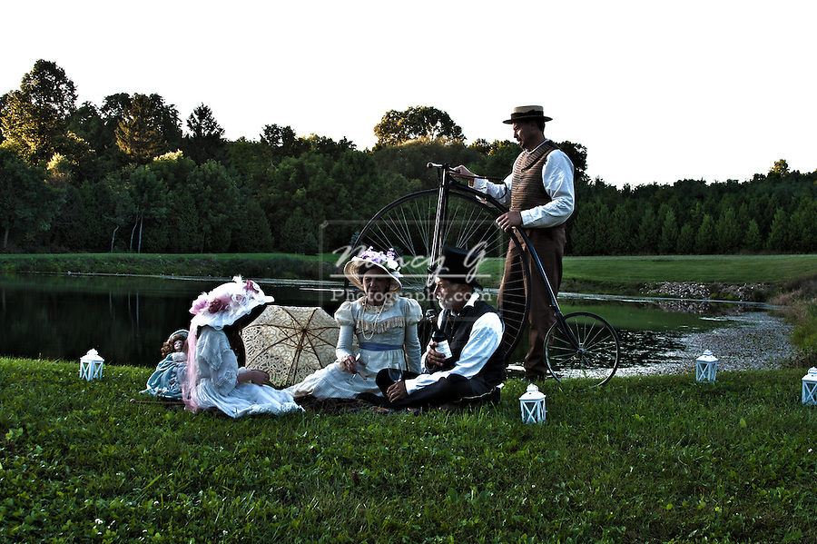 Victorian family with a bicycle next to a pond