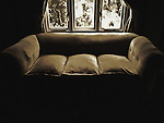 An old chesterfield sofa infront of a living room window with sunlight coming in