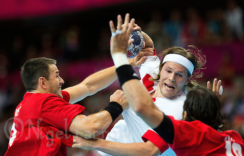 29 JUL 2012 - LONDON, GBR - Mikkel Hansen (DEN) of Denmark (centre in white) finds his path to goal blocked by Ferenc Ilyés (HUN) (left) and Laszlo Nagy (HUN) of Hungary (right) during the men's London 2012 Olympic Games Preliminary round handball match at The Copper Box in the Olympic Park, in Stratford, London, Great Britain (PHOTO (C) 2012 NIGEL FARROW)