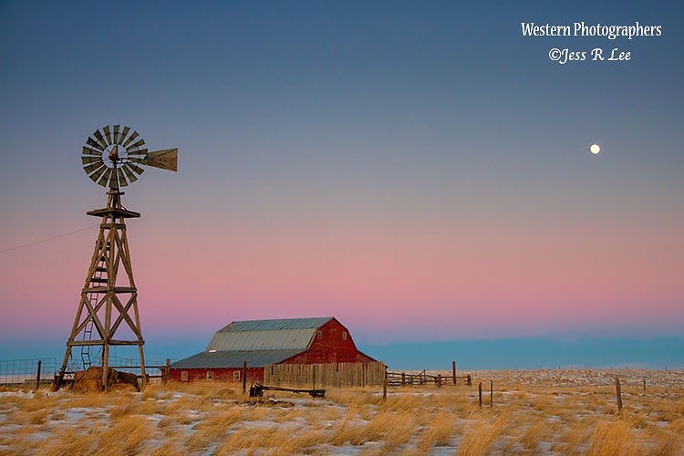 A photograph of an old red barn and windmill, with snow covered fields at sunrise.