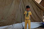 DOMIZ, IRAQ: A young Syrian refugee stands by a tent in the Domiz refugee camp...Over 7,000 Syrian Kurds have fled the violence in Syria and are living in the Domiz refugee camp in the semi-autonomous region of Iraqi Kurdistan...Photo by Ari Jalal/Metrography