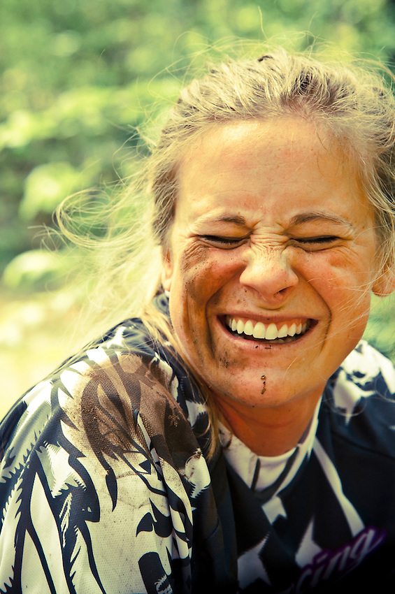 Smiling female girl mountain biker with dirt on her face after a crash.