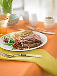 Slices of roasted lamb with au gratin potatoes and green beans. On a table with tablecloth, table setting, flowers.