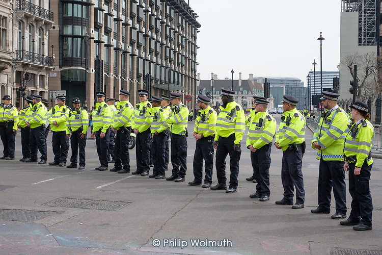 Police officers cordon off Portcullis House and the Houses of Parliament as Extinction Rebellion climate change campaigners marching from Marble Arch arrive at Parliament Square, London.