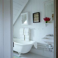 A free-standing bath sits below the sloped wood paneled ceilings in this whitewashed bathroom.