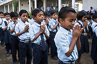 Children from ages 4 to 16 say a prayer during morning assembly in the Vasudha Vidya Vihar school in Khargone, Madhya Pradesh, India on 12 November 2014. This school was built using the Fairtrade Premium funds of the Fairtrade cotton farmers and producers in Karhi village of Khargone. Photo by Suzanne Lee for Fairtrade