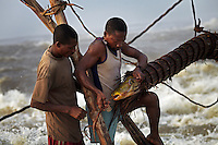 Fishermen remove a huge carp from a trap attached to a wooden scaffold at Boyoma Falls (known locally as Wagenia Falls). This is the last of seven cataracts below which the Lualaba River becomes the Congo. For generations members of the Wagenia tribe have built and maintained these structures in the same manner described by Henry Morton Stanley, after whom the falls were also once named, during his navigation of the Congo in 1874-77.