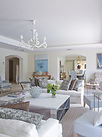 The living room has been put together in a simple style with touches of ornamentation such as the white-painted chandelier hanging above the coffee table