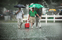 Saratoga Springs, NY  Patrons walk through a heavy downpour of rain from a thunderstorm at the New York Racing Association thoroughbred racing track here..©Mitch Wojnarowicz CF 00477