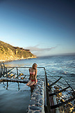 USA, California, Big Sur, Esalen, a woman sits at the Baths and looks out on the Big Sur coastline at sunset, the Esalen Institute