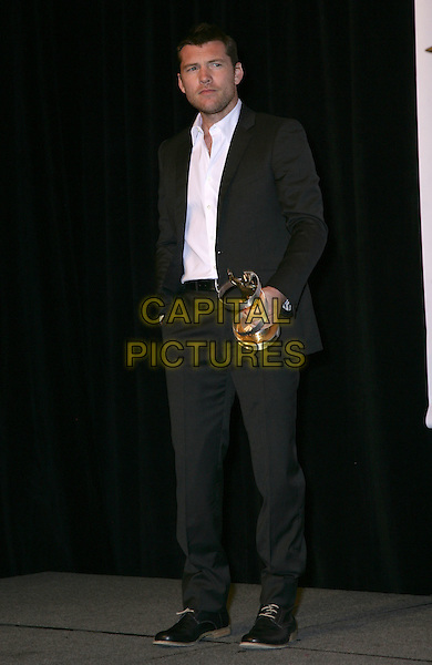 SAM WORTHINGTON .SHOWEST Final Night Talent Awards at the Paris Resort Hotel and Casino,  Las Vegas, Nevada , USA,.18th March 2010..full length black suit white shirt award winner trophy  shoes hand in pocket .CAP/ADM/MJT.© MJT/AdMedia/Capital Pictures.
