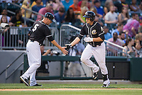 Jason Coats (17) of the Charlotte Knights slaps hands with third base coach Ryan Newman (5) as he rounds the bases after hitting a home run against the Columbus Clippers at BB&T BallPark on May 27, 2015 in Charlotte, North Carolina.  The Clippers defeated the Knights 9-3.  (Brian Westerholt/Four Seam Images)