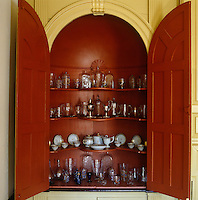A display of glassware, porcelain and silverware inside a recessed built-in cupboard in the drawing room