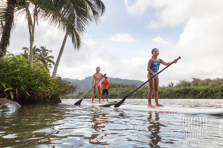 A family enjoys learning how to standup paddle on the Wailua River, Kaua'i.