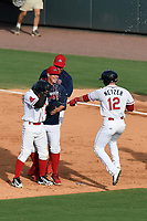 Teammates surround Santiago Espinal (2) of the Greenville Drive, including Brett Netzer (12), after he hit a walk-off single for a 2-1 win in a game against the Rome Braves on Sunday, August 13, 2017, at Fluor Field at the West End in Greenville, South Carolina. (Tom Priddy/Four Seam Images)