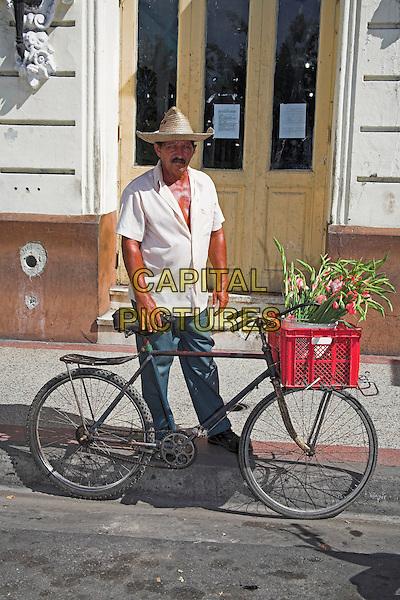 Traditional flower seller standing beside bicycle, Parque Cespedes, Santiago de Cuba, Cuba