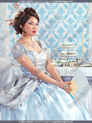 Beautiful asian lady in a luxurious blue dress sitting at a tea party table with a fan