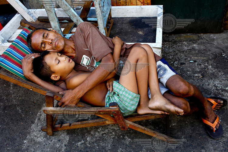 A man and a boy sleep, huddled together on a deck chair.