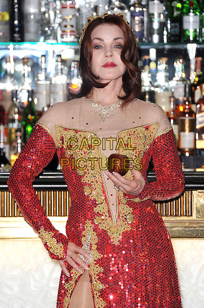 Priscilla Presley .The press launch for The New Wimbledon Theatre production of 'Snow White And The Seven Dwarfs', The Savoy Hotel, London, England..September 26th, 2012.panto costume half length gold red dress crown sequins sequined slit split hand on hip apple .CAP/BEL.©Tom Belcher/Capital Pictures.