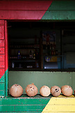 JAMAICA, Port Antonio. Coconuts lined up on the window of the Willow Wind Bar.
