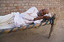 Old Gujarat man laying on bed out on street in a small village, Dasada, Gujarat, India --- Model Released