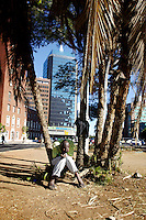 A man holds his head in his hands. Behind him stands the Karigmombe Centre, one of the 1980s skyscrapers built in more optimistic times after independence.