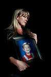 April Brune poses for a portrait while holding a portrait of her son Ryan at her Reno, Nevada home, February 3, 2014. Ryan Brune died from leukemia he was diagnosed with while they lived in Fallon, Nevada.