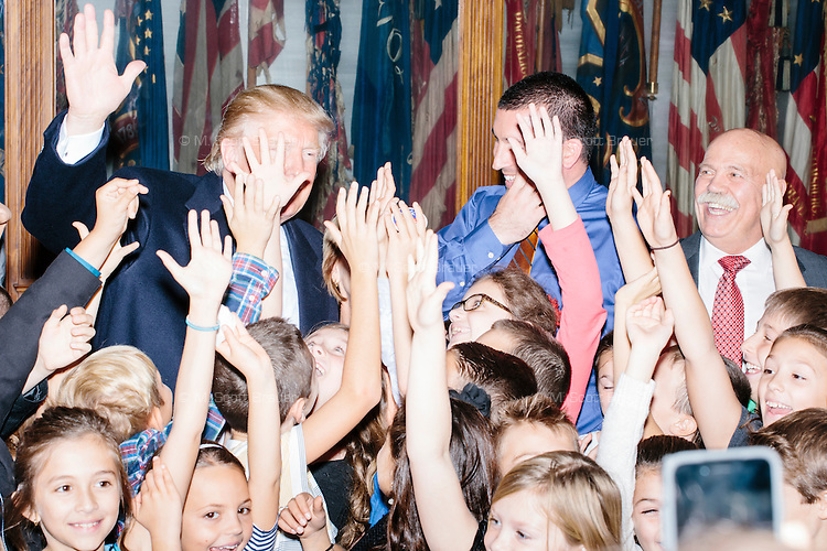 Real estate mogul and Republican presidential candidate Donald Trump poses for pictures with children in the New Hampshire State House after officially filing his candidacy in the New Hampshire primary in Concord, New Hampshire.