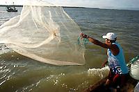 O pescador artesanal José Alfredo de Souza Costa, 31, pescador desde os doze anos, conhecido como Caburé (pássaro da região), lança sua rede para capturar peixes de baixo valor comercial para servirem de isca na pescaria com espinhel (armadilha com grande número de anzóis), nas proximidades da praia de Paxicú na Reserva Extrativista Marinha Mãe Grande localizada no litoral do Pará, na foz do rio Amazonas.<br /> Curuça, Pará, Brasil<br /> Foto: Paulo Santos<br /> 18/02/2010