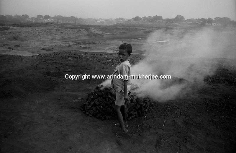 A boy standing in front of burning coal. Pirated raw coals are being burnt before selling it at the illegal coal market Jharia, Jharkhand, India. Arindam Mukherjee