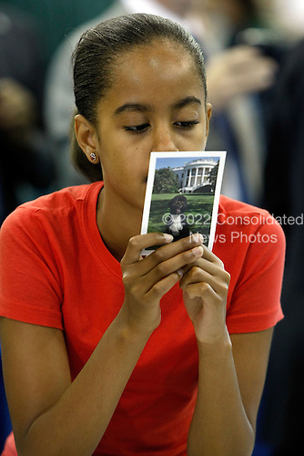 "Washington, DC - June 25, 2009 -- Malia Obama, daughter of U.S. President Barack Obama, reads the back of a card bearing the photograph of the first dog Bo while working with volunteers and members of Congress to stuff backpacks with books and food during a United We Serve event at Fort McNair June 25, 2009 in Washington, DC. Helping to fill 10,000 backpacks for children of military servicemen and women, the first family stuffed copies of ""The Lightning Thief,"" by Rick Riordan, and ""The Penderwicks,"" by Jeanne Birdsall into backpacks along with food items and a personal letter from the president and the first lady. .Credit: Chip Somodevilla - Pool via CNP"