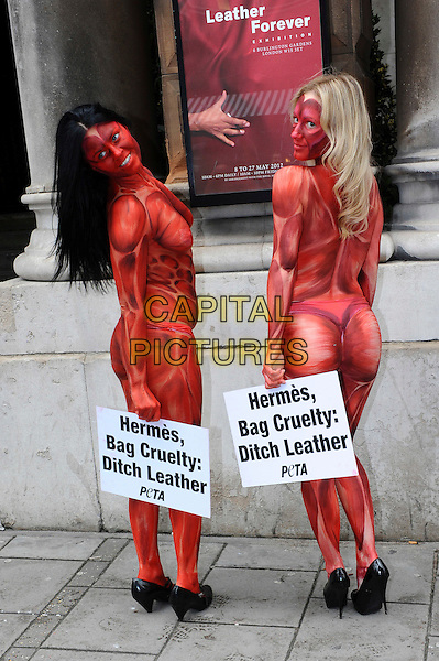 "Painted to resemble bloodied and skinned people, three models representing PETA converged outside the opening of the 'Herme's Leather Forever' exhibition. They held signs reading ""Herme's, Bag Cruelty: Ditch Leather, while other PETA members handed out leaflets to passers by  at the Royal Academy of Arts at Burlington Gardens, London England 08th May 2012..full length red paint naked nude signs posters back behind rear looking over shoulder .CAP/CJ.©Chris Joseph/Capital Pictures."