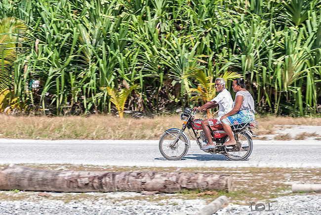 An i-Kiribati couple riding a motorcycle on the remote island of Kiritimati in Kiribati.