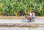 An i-Kiribati couple riding a motorcycle on the remote island of Kiritimati in Kiribati.