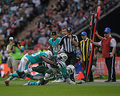 04.10.2015. Wembley Stadium, London, England. NFL International Series. Miami Dolphins versus New York Jets.  Jets' Running Back Zac Stacy [#30] is tackled by Dolphins' Strong Safety Reshad Jones [#20] and Dolphins' Outside Line Backer Jelani Jenkins [#53].