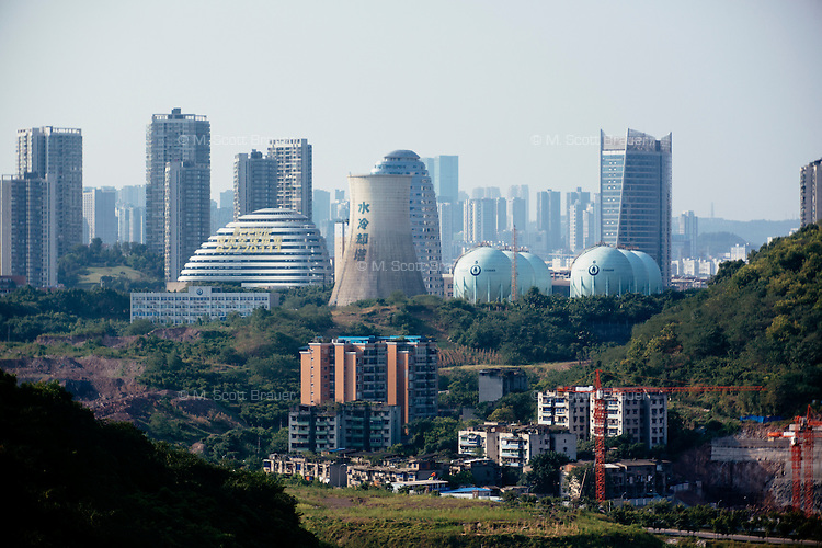 Futuristic buildings and a powerplant stand among apartment buildings in northeastern Chongqing, China.