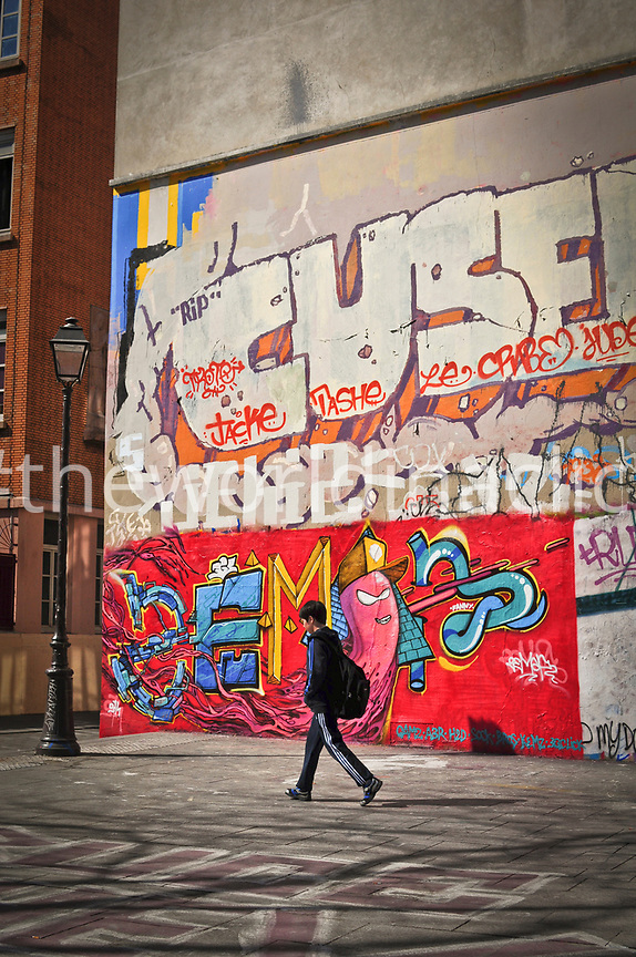 FRANCE, Paris, a boy is walking in Canal Saint Martin in Paris, Graffiti wall in the background