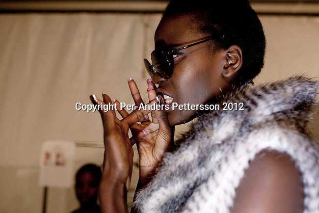 JOHANNESBURG, SOUTH AFRICA  MARCH 10: A model bites her nails backstage before a show for the designer Gavin Rajah at the Joburg Fashion Week on March 10 2012, at the Hyde Park Mall in Johannesburg, South Africa. South Africa's finest designers showed their 2012 Autumn & Winter collections during the 4 day event. (Photo by Per-Anders Pettersson)