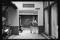 A woman helps an elderly man at a traditional alleyway in Suzhou, Jiangsu province, China, August, 2012. Suzhou is famous for its canals, stone bridges, pagodas, and meticulously designed gardens. (Leica M6, 50mm f2, Kodak TRI-X 400)